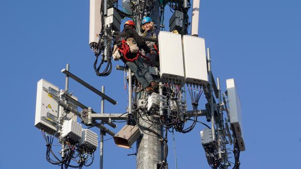 A crew from Verizon installs 5G equipment on a tower in Orem