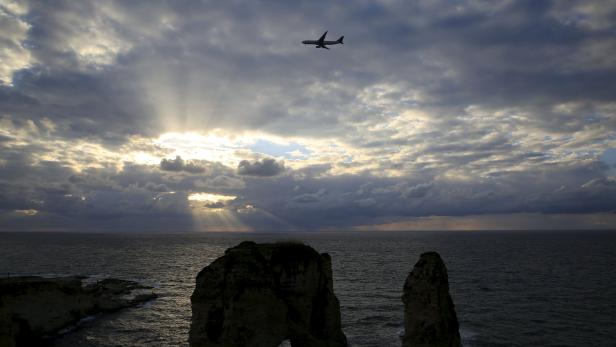 An airplane flies over the Pigeons' Rock as storm clouds loom during sunset in Beirut