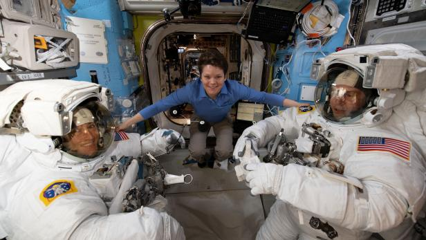 Astronaut Anne McClain assists fellow astronauts Christina Koch and Nick Hague ahead of a set of upcoming spacewalks at the International Space Station