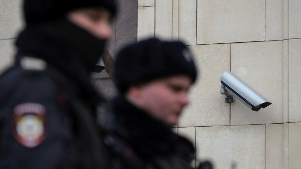 FILE PHOTO: Police officers walk past a CCTV camera in central Moscow