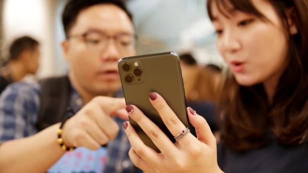 FILE PHOTO: A customer touches Apple's new iPhone 11 Pro Max after it went on sale at the Apple Store in Beijing
