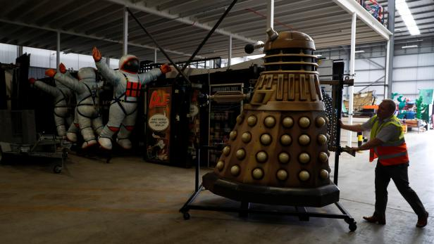 A worker pushes a model of a Dalek past other figures used in the illuminations at The Lightworks in Blackpool, Britain