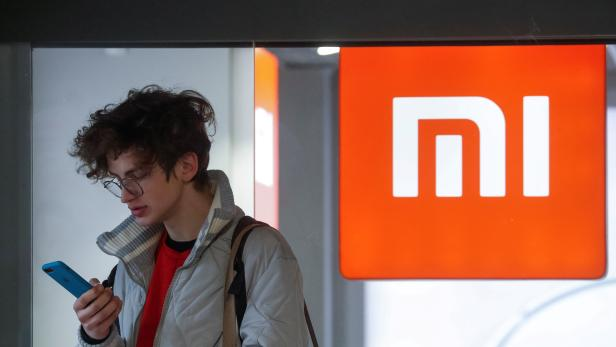 FILE PHOTO: A man uses his smartphone next to the Xiaomi brand's store in central Kiev