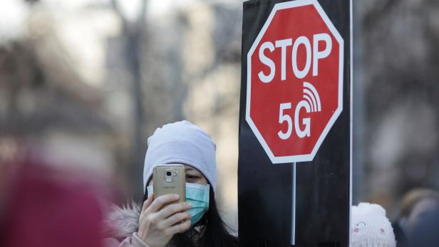 """A woman uses her mobile phone while holding a placard reading """" STOP 5G"""" during a protest against 5G technology"""