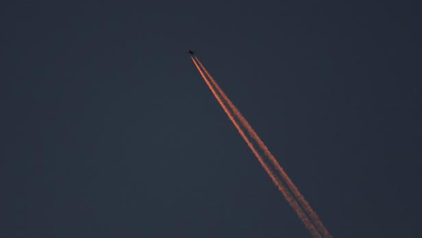 A passenger plane leaves behind contrails as it flies in the skies over London Luton Airport, Luton