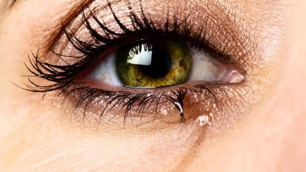 Macro of single, tearful eye. belonging to very unhappy woman