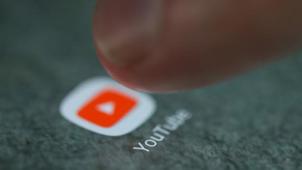 The YouTube app logo is seen on a smartphone in this illustration
