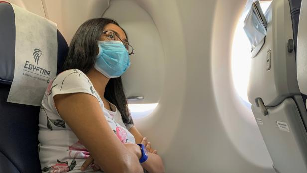 A passenger wears a protective mask on an Egyptair flight from Luxor to Cairo, following the outbreak of the coronavirus disease (COVID-19), in Egypt