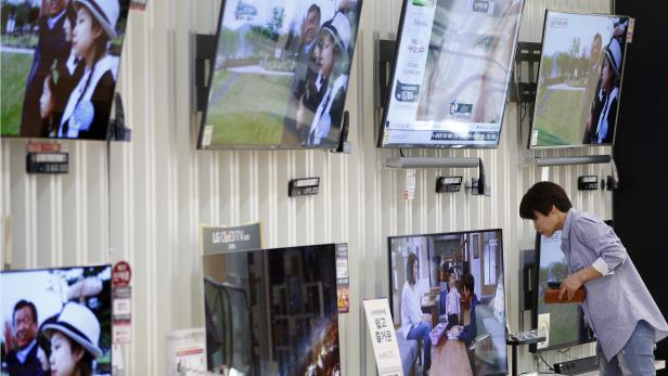 A woman looks at a LG Electronics' OLED TV at its store in Seoul