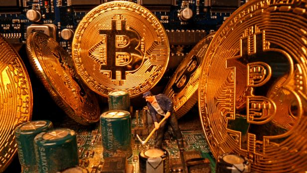 A small toy figure and representations of the virtual currency Bitcoin stand on a motherboard in this picture illustration