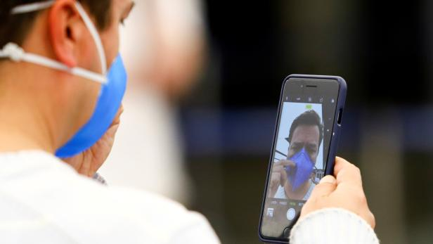 A man in a face mask takes a selfie at Ministro Pistarini International Airport in Buenos Aires