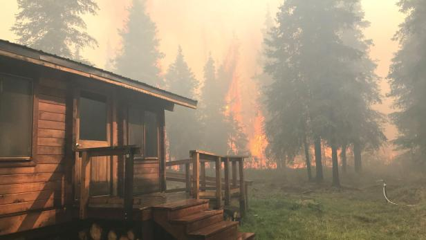 Firefighters from the Chugach National Forest work to protect the Romig Cabin on Juneau Lake from the Swan Lake Fire near Cooper Landing