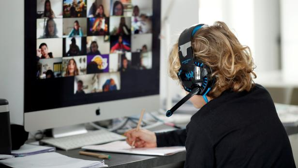 FILE PHOTO: A student takes classes online with his companions using the Zoom APP at home