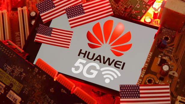 FILE PHOTO: The U.S. flag and a smartphone with the Huawei and 5G network logo are seen on a PC motherboard in this illustratio