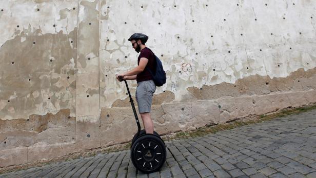 A tourist rides on a Segway through a street in central Prague