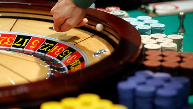 Instructor Daisuke Sato spins a ball in the spinning wheel on a roulette table at Japan Casino School in Tokyo