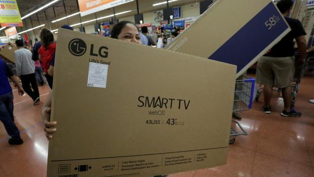 A shopper carries a Smart TV during the kick-off of the 'El Buen Fin' (The Good Weekend) holiday shopping season, at a Walmart store in Monterrey