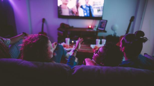 Multi-ethnic teenage friends watching TV together at hangout house