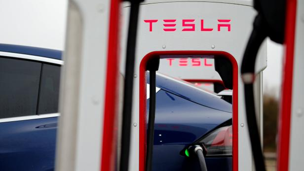 A driver recharges the battery of his Tesla car at a Tesla Super Charging station in a petrol station on the highway in Sailly-Flibeaucourt