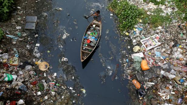FILE PHOTO: A man on a boat collects plastic materials from dirty water in Dhaka