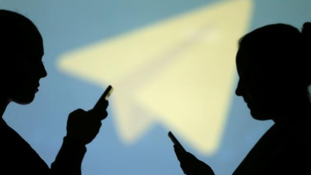 Silhouettes of mobile users are seen next to a screen projection of Telegram logo in this picture illustration