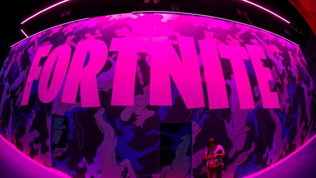 FILE PHOTO: An attendee stops to text next to Epic Games Fortnite sign at E3, the annual video games expo revealing the latest in gaming software and hardware in Los Angeles