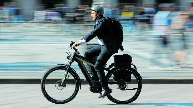 FILE PHOTO: A man rides an electric bicycle, also known as an e-bike, in downtown Milan