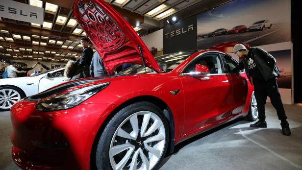 A visitor views the Tesla Model 3 electric vehicle at the Canadian International Auto Show in Toronto