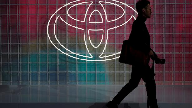 FILE PHOTO: A man walks past a Toyota logo at the Tokyo Motor Show