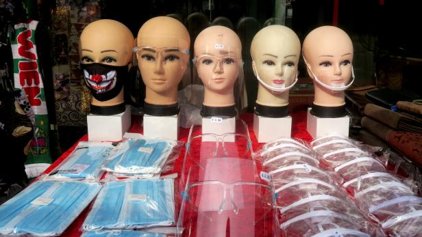 Protective face masks and face shields are on display at a market in Vienna