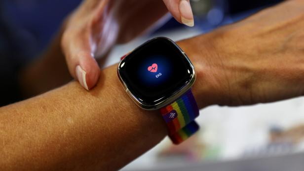 An employee uses an electrocardiogram function on a Fitbit smartwatch at the IFA consumer technology fair, in Berlin