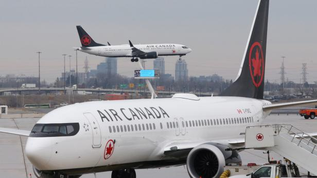 FILE PHOTO: An Air Canada Boeing 737 MAX 8 from San Francisco approaches for landing at Toronto Pearson International Airport over a parked Air Canada Boeing 737 MAX 8 aircraft in Toronto