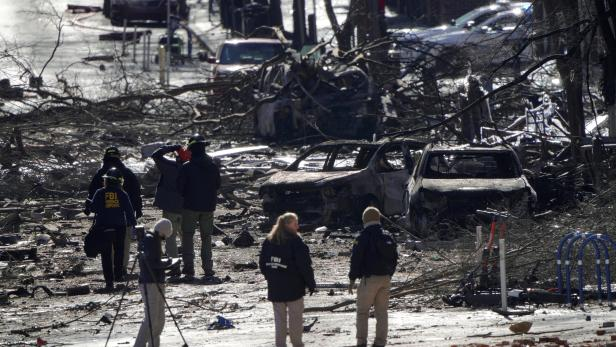 Investigators work near the site of an explosion on 2nd Avenue that occurred the day before in Nashville