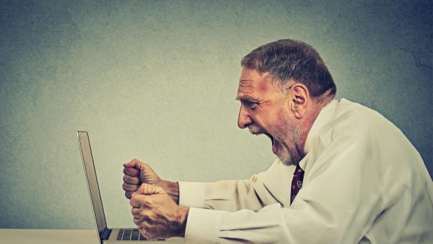 Angry senior business man working on computer screaming
