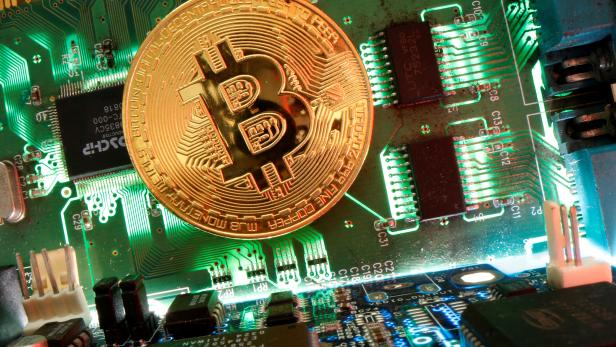 Representation of the virtual currency Bitcoin is seen on a motherboard in this picture illustration