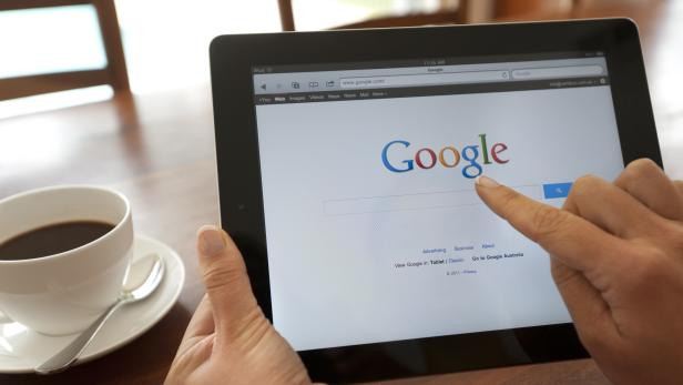 Female hand holding an ipad showing Google.