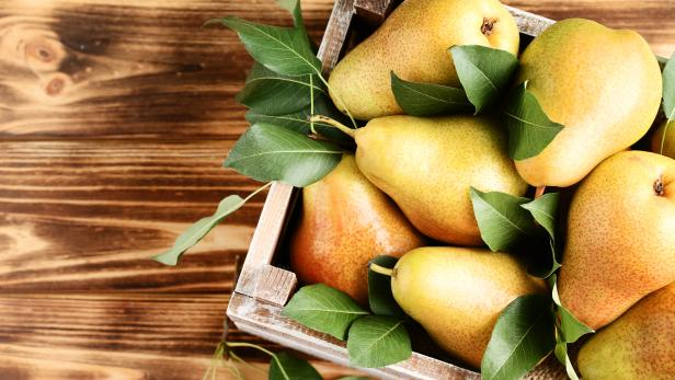 Ripe pears and green leafs in crate on brown wooden table