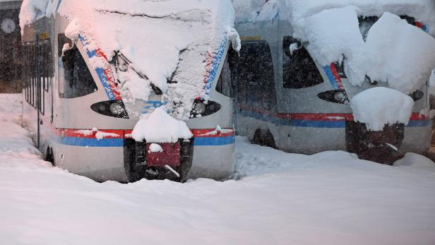 Two regional trains that are covered with snow stand at the train station in Berchtesgaden