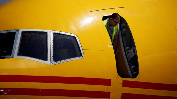 A technician looks out of the door of a DHL Boeing 757 aircraft before a charity fundraising event in which teams compete by pulling the aircraft for twenty metres at the Safi Aviation Park in Safi