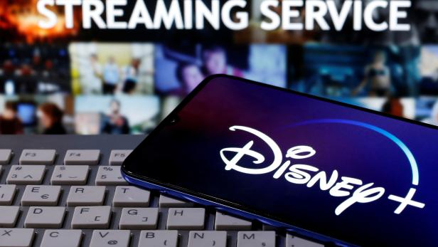 """FILE PHOTO: Smartphone with displayed """"Disney"""" logo is seen on the keyboard in front of displayed """"Streaming service"""" words in this illustration"""