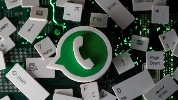 A 3D printed Whatsapp logo and keyboard buttons are placed on a computer motherboard