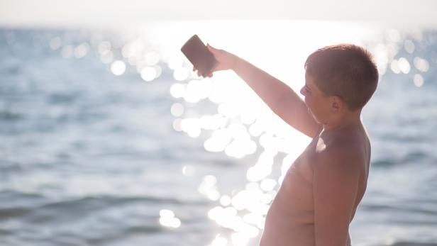boy on the beach making selfie