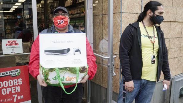 A man poses outside a GameStop store with his purchase of a Sony PS5 gaming console