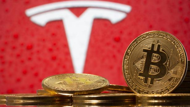 Representations of virtual currency Bitcoin are seen in front of Tesla logo in this illustration