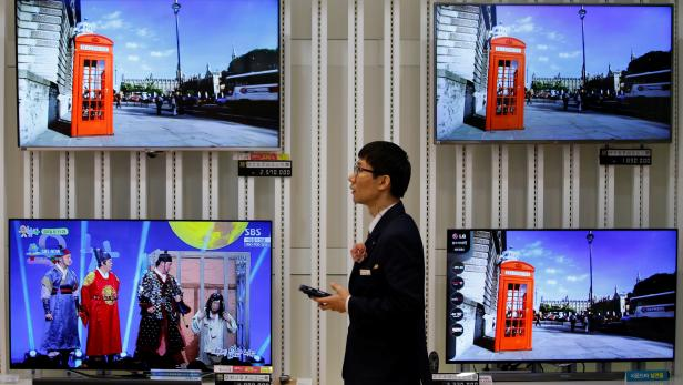 FILE PHOTO: An employee uses his mobile phone in front of LG Electronics' organic light-emitting diode TV sets, which are made with LG Display flat screens, at its store in Seoul