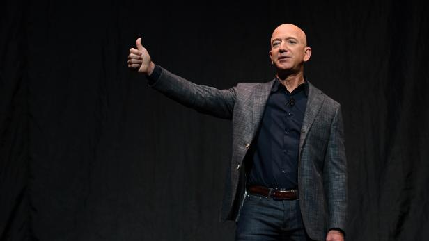 FILE PHOTO: Founder, Chairman, CEO and President of Amazon Jeff Bezos gives a thumbs up as he speaks during an event about Blue Origin's space exploration plans in Washington