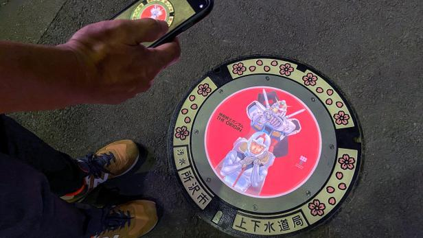 A passerby using a smartphone takes a photo of an illuminated manhole cover with designs of popular animation character Gundam, on the street in Tokorozawa, near Tokyo