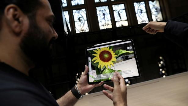 FILE PHOTO: Attendees try out the new iPad Pro during an Apple launch event in the Brooklyn borough of New York