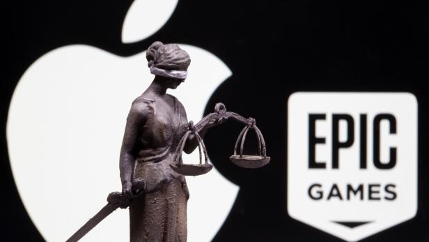 3D printed Lady Justice figure is seen in front of displayed Apple and Epic Games logos in this illustration photo