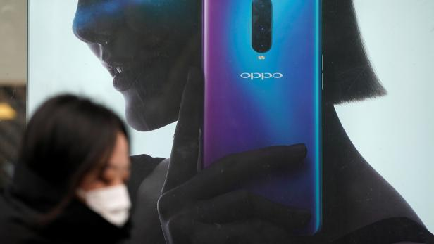 A woman walks past an Oppo advertisement at a shopping mall in Shanghai